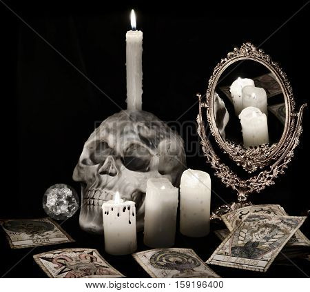 Vintage still life with scary skull, mirror, burning candles and the tarot cards in grunge retro style. Halloween concept, black magic ritual or spell with occult and esoteric symbols, divination rite