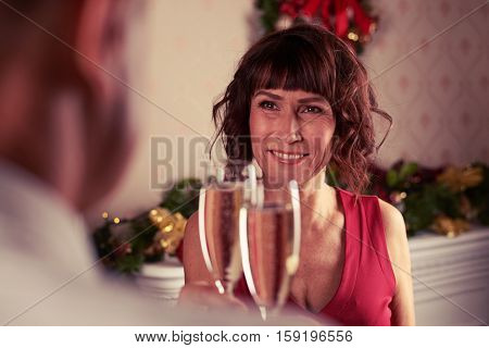 Close-up rack focus of senior couple celebrating together while standing near decorated fir tree and clinking champagne flutes. New Year or Christmas at midnight with champagne flutes make cheers