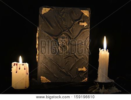 Mystic still life with black magic book and two burning candles. Halloween concept, black magic ritual or spell with occult and esoteric symbols, divination rite. Vintage objects on table