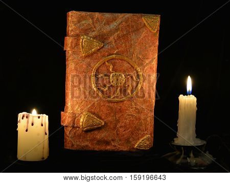 Old book of fairy tales with burning candles in the darkness. Halloween concept, black magic ritual or spell with occult and mystic symbols, divination rite. Vintage objects on table