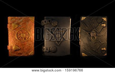Three black magic and vintage book in the darkness. Esoteric and occult objects of witch, divination ritual or Halloween concept