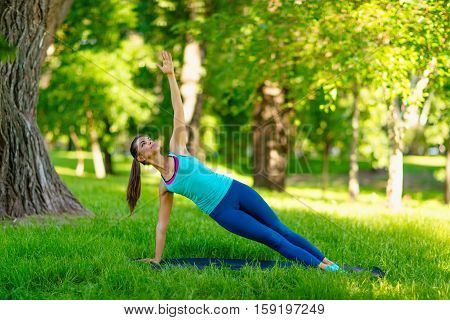 Yoga woman on green grass girl relaxing in a field. Yoga woman on green park girl doing gymnastics outdoors. Meditating woman in meditation in yoga pose practicing outdoors.