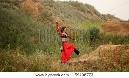 Oriental Beauty dance with a sword. Tribal style. Lovely girl in suit balancing on one foot outdoors. Sand dunes. Nomads.