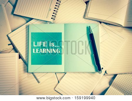 Manny empty notebook paper and note pad background with one blue book and life is learning quotes vintage retro color tone