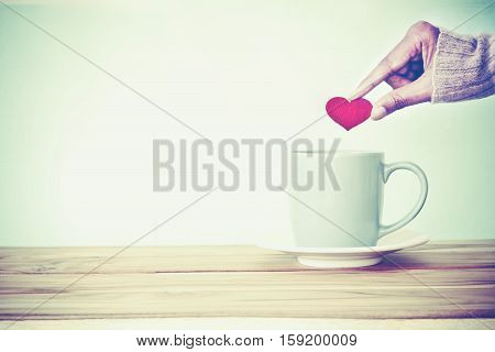 hand holding red heart shape put into a Coffee cup mug on wooden table Romance and love valentines day background . Happy and relax concept