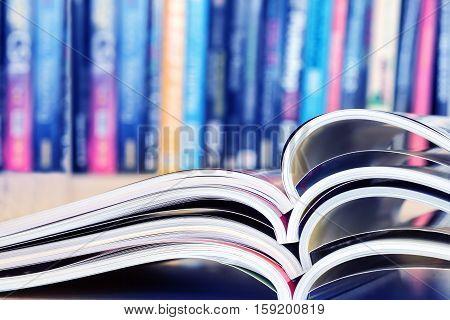 close up stacking of opened magazine with blurry bookshelf background extremely shallow DOF