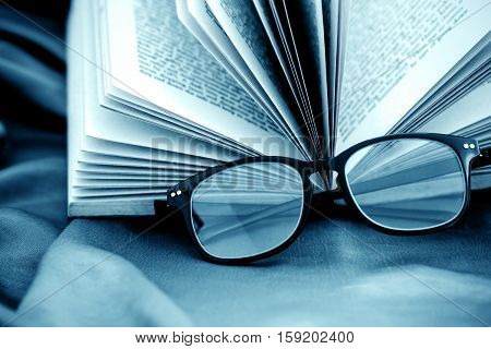 selective focus of the reading Eyeglasses wiht opened book
