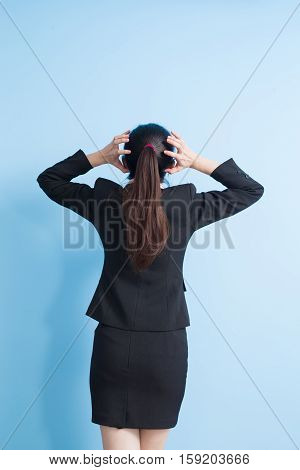 back view of business woman think with isolated blue background
