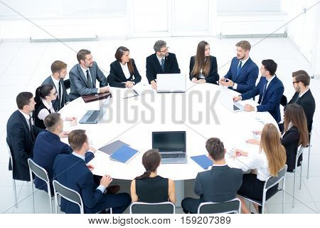 Businesspeople Sitting At Conference Round Table At The Meeting