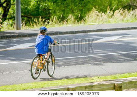 young happy preteen child boy riding a bicycle on urban background, boy crossing a street by bike