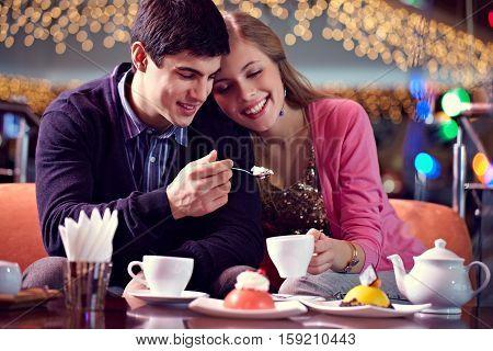 Loving couple enjoying dessert together at cafe