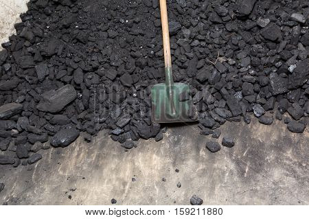 Black Coal And Shovel Lying On A Pile In House Basement