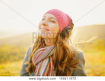 Young Beautiful Woman Smiling And Enjoying Music In Fall Season