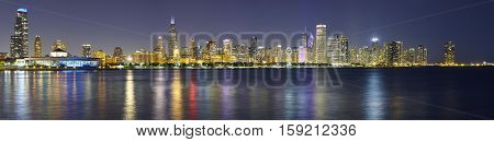 Night Panoramic Picture Of Chicago City Skyline With Reflection In Lake Michigan