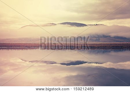 Retro Toned Foggy Morning Over Lake In Grand Teton National Park, Usa.