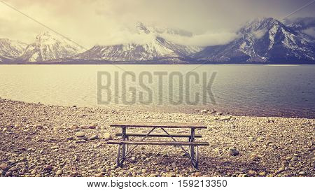 Retro Stylized An Empty Bench With Beautiful View Over Lake, Wyoming, Usa.