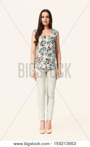woman with straight hair style in office print floral summer blouse and trousers high heel shoes going full body length isolated on white