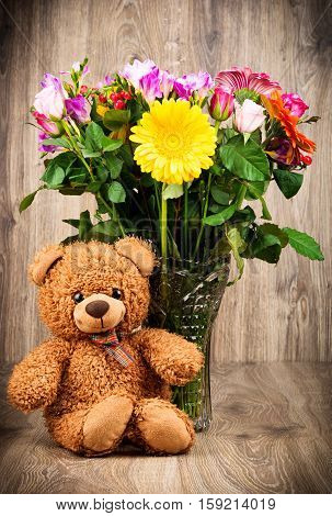 A teddy bear and bright flowers in the vase on wooden background