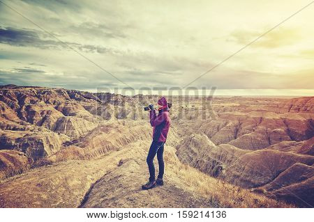 Vintage toned photo of a female photographer taking pictures at sunset Badlands National Park South Dakota USA.