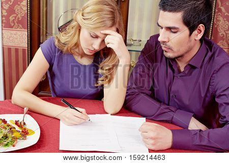 Marriage couple signing a prenuptial agreement in restaurant