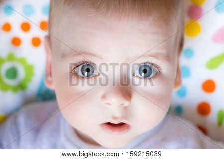 Close up of a baby boy face with big blue eyes looking wondrous into camera