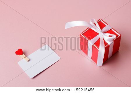 Valentine day composition: red gift box with bow and credit / visiting card template with clamp on light pink background.