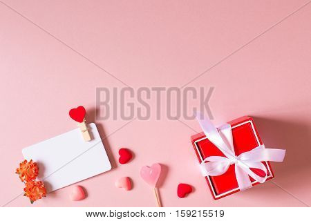 Valentine day composition: red gift box with bow credit / visiting card template with clamp spring flowers candy and small hearts on light pink background. Top view.