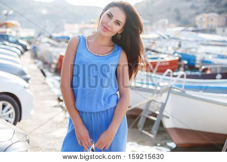 Slim beautiful brunette woman with thick long hair and brown eyes,light makeup and red lipstick,wears large gold earrings,dressed in a summer suit of blue,posing in the summer near the sea on a pier near yachts and boats