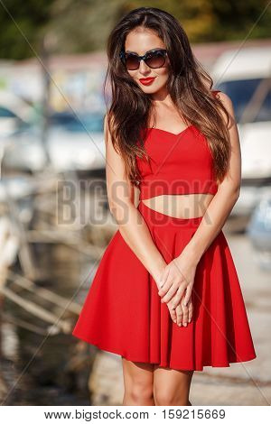 Young beautiful brunette woman with thick long hair and brown eyes,a beautiful figure,light makeup and red lipstick,dark glasses,dressed in a summer skirt and vest red,posing in the summer near the sea on a pier near yachts and boats