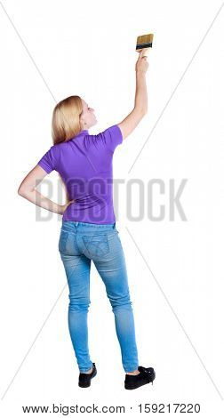 Back view of a girl who paints the paint roller. rear view people collection. backside view of person.  Long-haired blonde in the purple shirt put her hands to the side and color.
