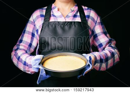 Freshly Baked Cheesecake In Hands On Black Apron Background