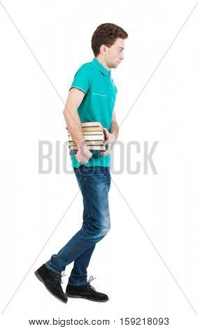 Back view of going  handsome man carries a stack books. walking young guy . Rear view people collection. Isolated over white background. Sad man in green T-shirt goes to the left with a stack of books