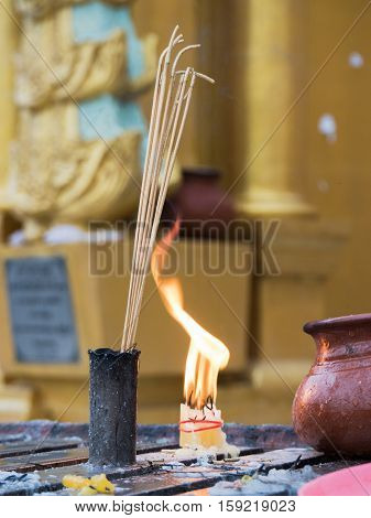 Joss sticks and a bundle of candles burning at dawn in front of a golden stupa at the Shwedagon Pagoda in Yangon Myanmar. Shallow depth of field with the joss sticks in focus.