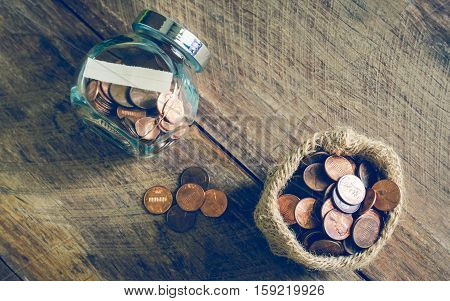 One cent coins in glass jar and gunny bag - vintage style effect