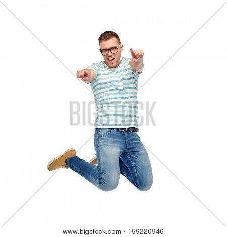 happiness, freedom, motion and people concept - happy young man jumping in air and pointing fingers to you