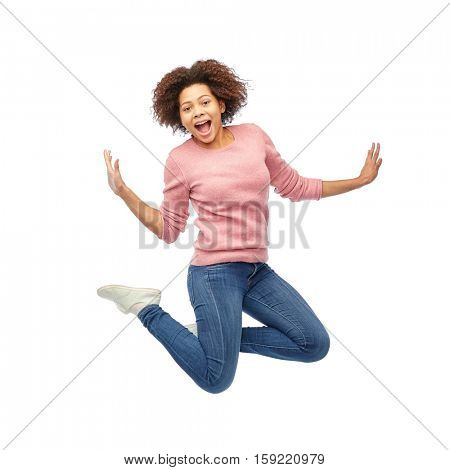 people, motion and action concept - happy african american young woman jumping over white