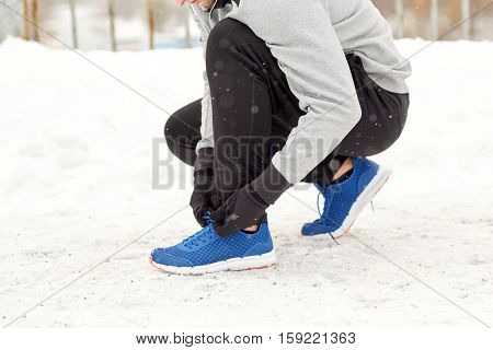 fitness, sport, people, music and healthy lifestyle concept - young man in earphones tying shoe on winter bridge