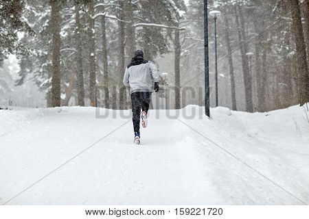 fitness, sport, people, season and healthy lifestyle concept - young man running on snow covered winter road in forest