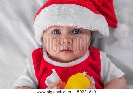 Christmas toddler baby girl in Santa hat and yellow rubber duck