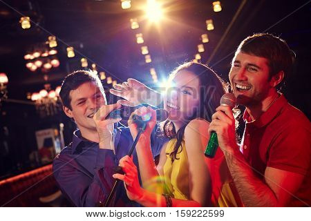 Three cheerful friends singing karaoke in club