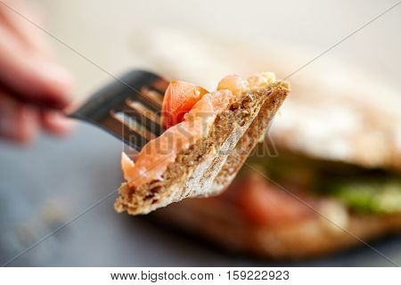 food, dinner and people concept - hand of person eating salmon panini sandwich with tomatoes and cheese using fork and knife at restaurant