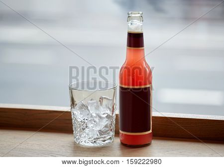 drinks concept - bottle of lemonade and glass with ice on cafe table