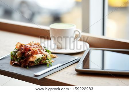 food, dinner, haute cuisine and eating concept - prosciutto ham salad on stone plate with matcha green tea latte and tablet pc computer at restaurant