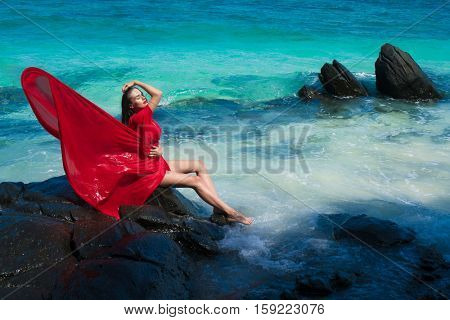 Beautiful sensual glamour woman in flying red dress with wet hair sitting on the rock over beautiful lagoon sea and tropical island background