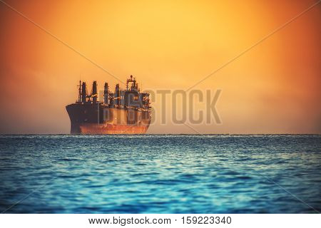 Morning sunrise over sea and sailing cargo ship near harbor