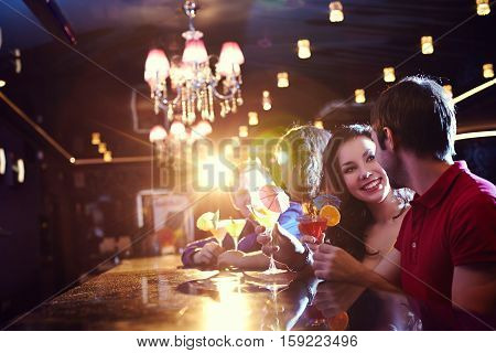 Young people flirting and drinking at bar counter