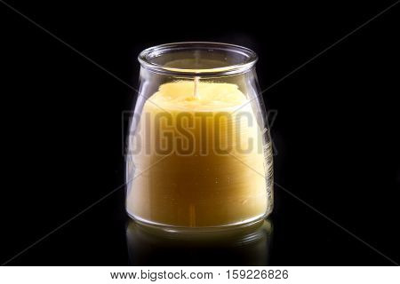 Beeswax candle (unlit) in a glass jar on a black background with a subtle reflection
