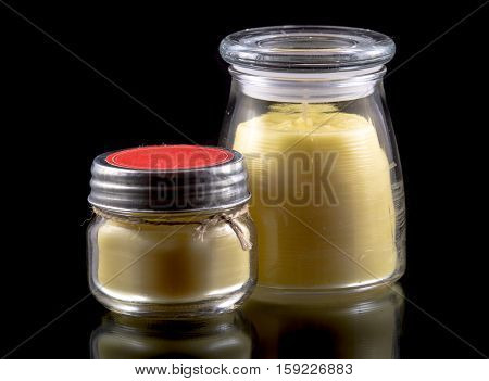 Two beeswax candles (unlit) in glass jars with lids one is a metal lid with a red surface