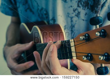 Part of man's hand while playing Ukelele - vintage style effect