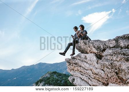 Man And Women Using Phone In Mountain In Montenegro, Freedom And Travel Cocept